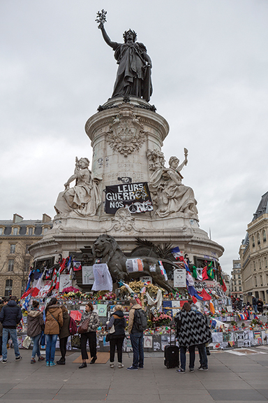 Paris, France - January 29, 2016: People mourn and stand in front of the memorial marking the terrorist attacks on 13 November 2015. Place de la Republique became the gathering spot to mourn the loss of life that occurred.