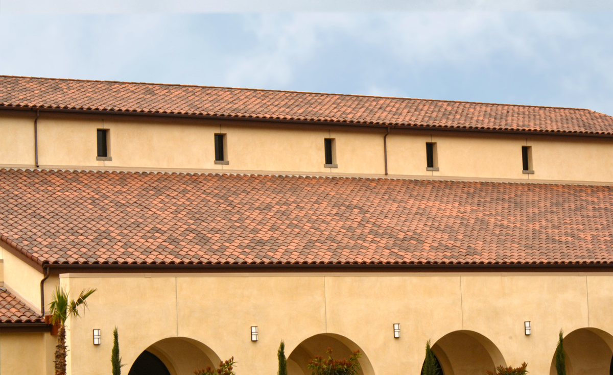 Roof detail of One Piece S Mission clay roof tile in B330-R Old Santa Barbara Blend with two piece eace line on Holy Trinity Catholic Church in Ladera Ranch, California