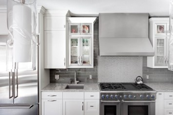 White kitchen cabinets and aluminum cabinet doors with glass next to a Thermador range