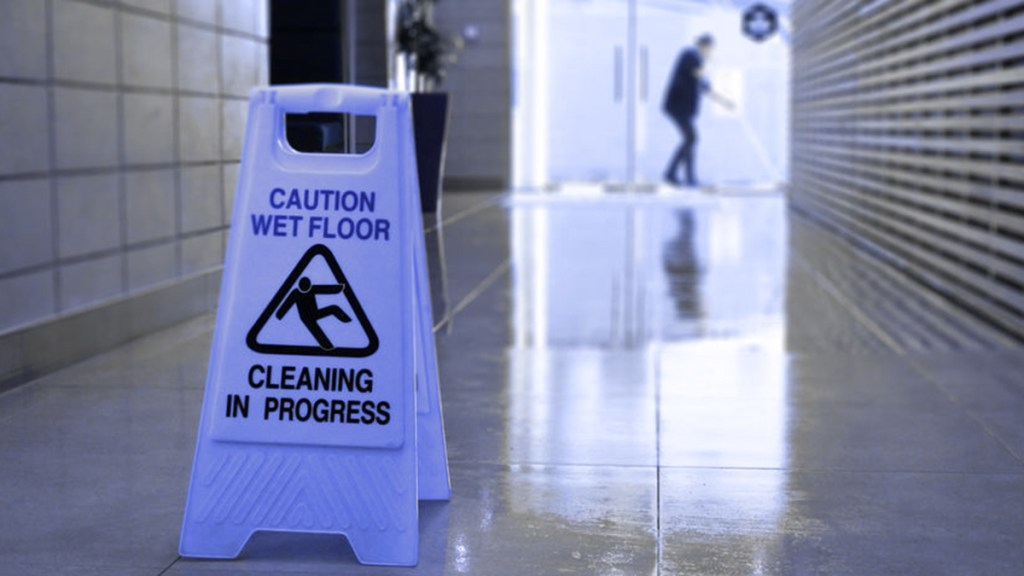 "A ""Cleaning in Progress"" sign and a worker mopping the floor so no one is injured."