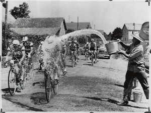 Cyclists getting doused with a bucket of water