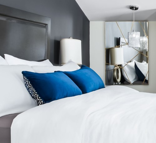 White linens on this luscious King Bed feature wall with Mirror vignette and sculptural Side Lamp and Pendant