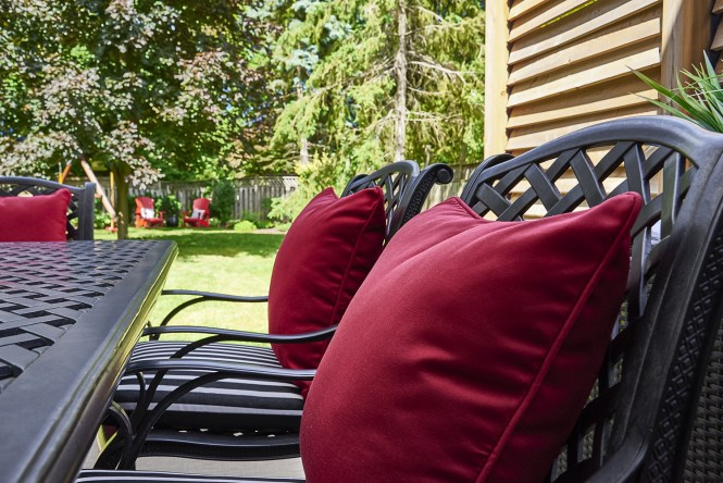 Cast Iron Deck Chairs, Red Pillows with Black and White Striped Seat Cushions