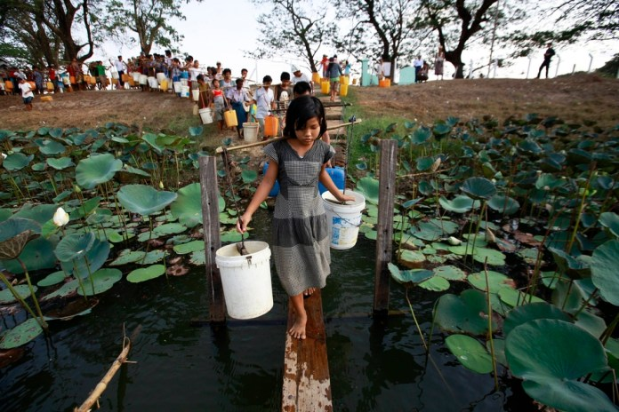 People line up to collect water at Yazarthingyan lake in Dala township, near Yangon May 12, 2013. Dala township is located near the sea and the only source of freshwater is from the inland lakes which have all dried up, with the exception of Yazarthingyan lake. According to the local authorities, the lake is only opened to locals once every three days, with over 1,000 people lining up to collect water when the authorities opened the lake from 4 pm to 5 pm. REUTERS/Soe Zeya Tun (MYANMAR - Tags: SOCIETY ENVIRONMENT TPX IMAGES OF THE DAY)
