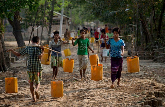 In this April 2, 2014 photo, residents of Dala, carry plastic containers filled with drinking water fetched from a natural water pond as others walk to collect water in the suburbs of Yangon, Myanmar. During the annual dry season in April and May, residents pay 10 kyat, 10 U.S. cents for each bucket of water and walk up to five kilometers (three miles) carrying the buckets full of water for the consumption of their families in this improvised neighborhood. (AP Photo/Gemunu Amarasinghe)