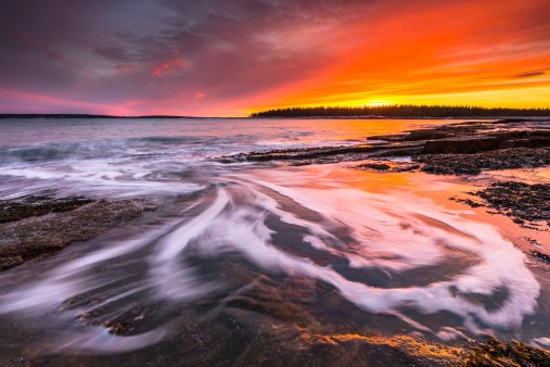 Waves swirl in a tide pool at sunset along the coast of Wonderland in Acadia National Park, Mount Desert Island, Maine.