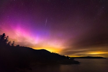 A meteor passes over the intense pink glow of the northern lights viewed in Acadia National Park, Mount Desert Island, Maine.