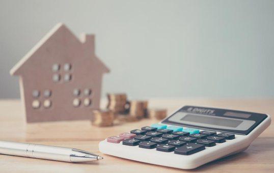imagem de uma mesa com uma calculadora, caneta dinheiro e casa de madeira em cima, representando o patamar da taxa selic e como isso impacta o mercado imobiliário