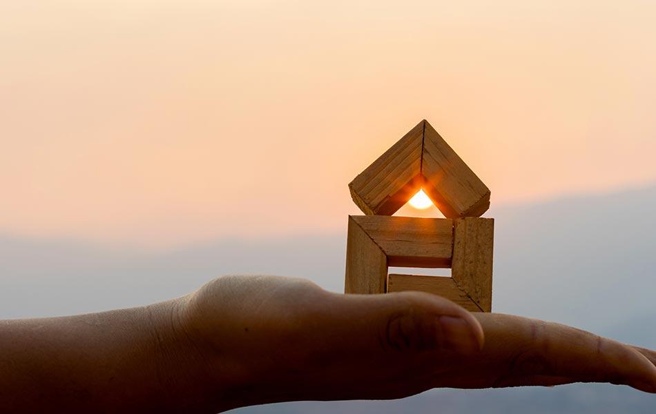 imagem com uma mão aberta e uma casa de blocos de madeira em cima, representando a oportunidade da queda da selic para compra do imóvel