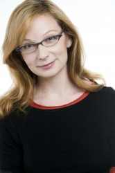 A white woman with medium length blondish brown hair and glasses, wearing a long-sleeve curved neck black shirt.