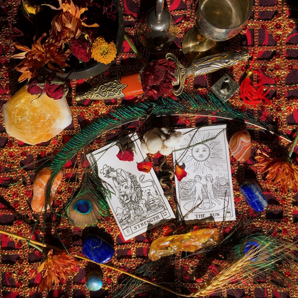 The Strength an Sun Tarot cards on a rich red and gold background surrounded by peacock feathers, lapis, amber, and grain