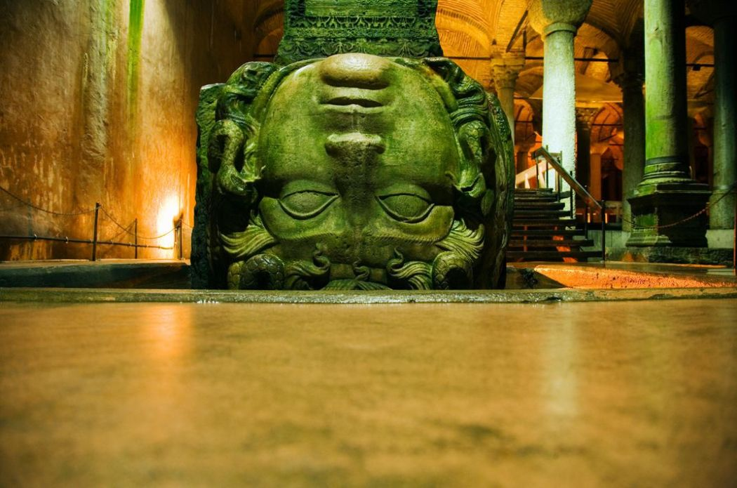 Goddess of the Betrayed. A stone Medusa head turned upside down in an act of disrespect to the Goddess, used as the base of a pillar at the bottom of a cistern, Istanbul, Turkey. Photo David Sutherland