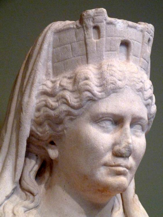 Megalesia, Magna Mater, Cybele. A white marble sculpture of a feminine person with a crown shaped like a turret. They have wavy hair parted in the middle.
