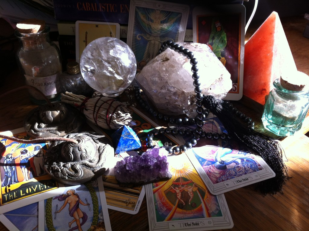 Wooden desktop with colorful tarot cards and crystals scattered around for tarot mentor class