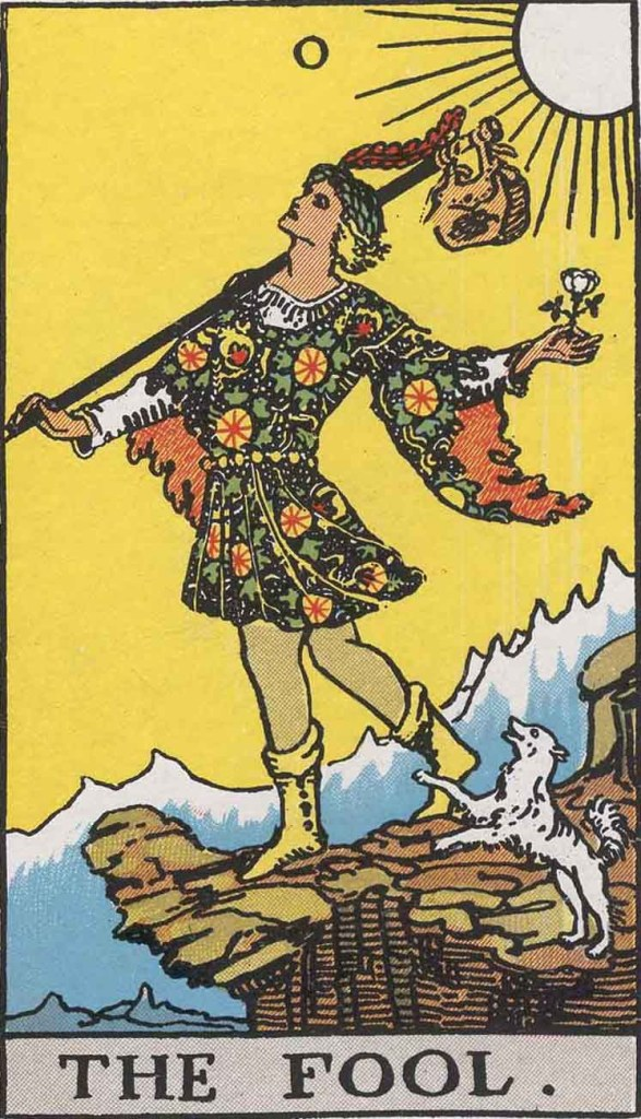The Fool Card, from the Pamela Colman Smith-Waite Tarot deck. An androgynous figure seems to dance along the edge of a cliff. They sky is yellow, and there's a small white dog at their feet. The carry a black staff with a bag at the end in one hand, and a white rose in the other.