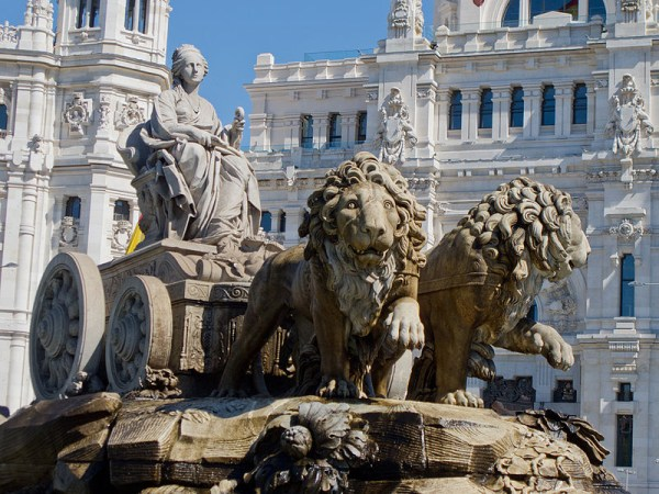 Cibeles Fountain, in the Plaza de Cibeles, Madrid Spain. A stone and marble sculpture of a feminine figure seated in a chariot pulled by two lions.