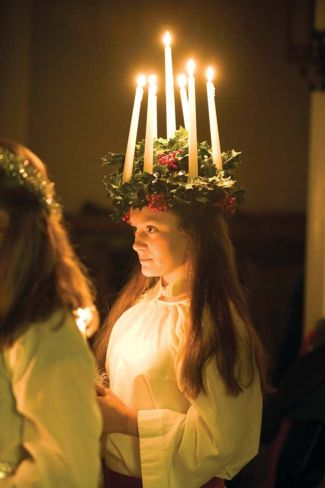 A young person with long red hair and pale skin wearing a white robe. They wear a crown made out of holly with deep green spiky leaves and bright red berries. Also on the crown are 7 tall, white candles with golden flames. This is a classic symbol worn by Priestesses during Imbolc rituals, Catholic practitioners celebrating Candlemas, and followers of St. Lucia, who also has a Holy Day at this time.