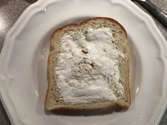 Spread cream cheese on sourdough bread