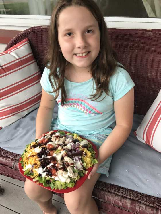 Daughter holding the BBQ Ranch Chicken salad