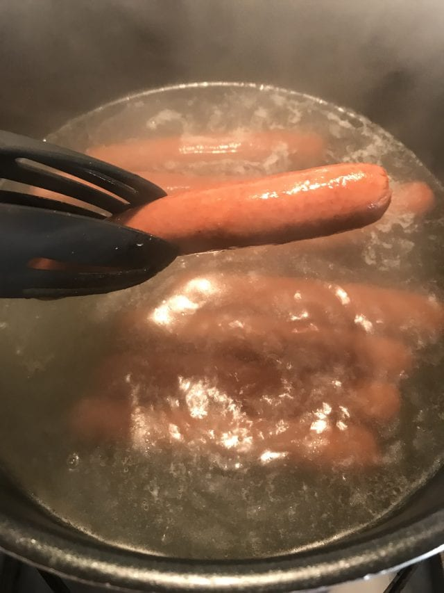 Cook hot dogs in boiling water.