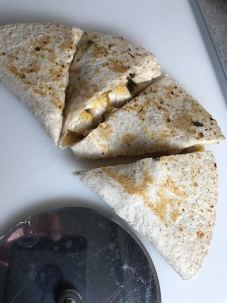 cut chicken quesadillas with a pizza cutter on a cutting board.