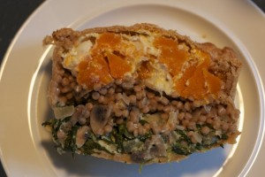 Slice of layered squash, barley adn spinach pie