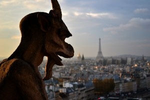 A Gargoyle on the towers of Notre Dame and the Eiffel Tower