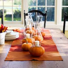 Use a colorful runner down your dining table and add a few hurricane vases and small pumpkins