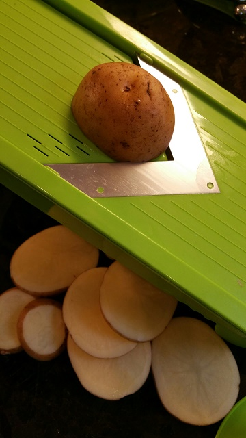 Using a Mandolin, slice potatoes and onions