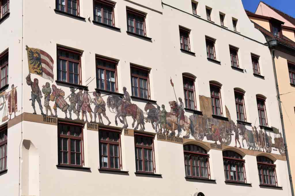 medieval procession mural on side of white building