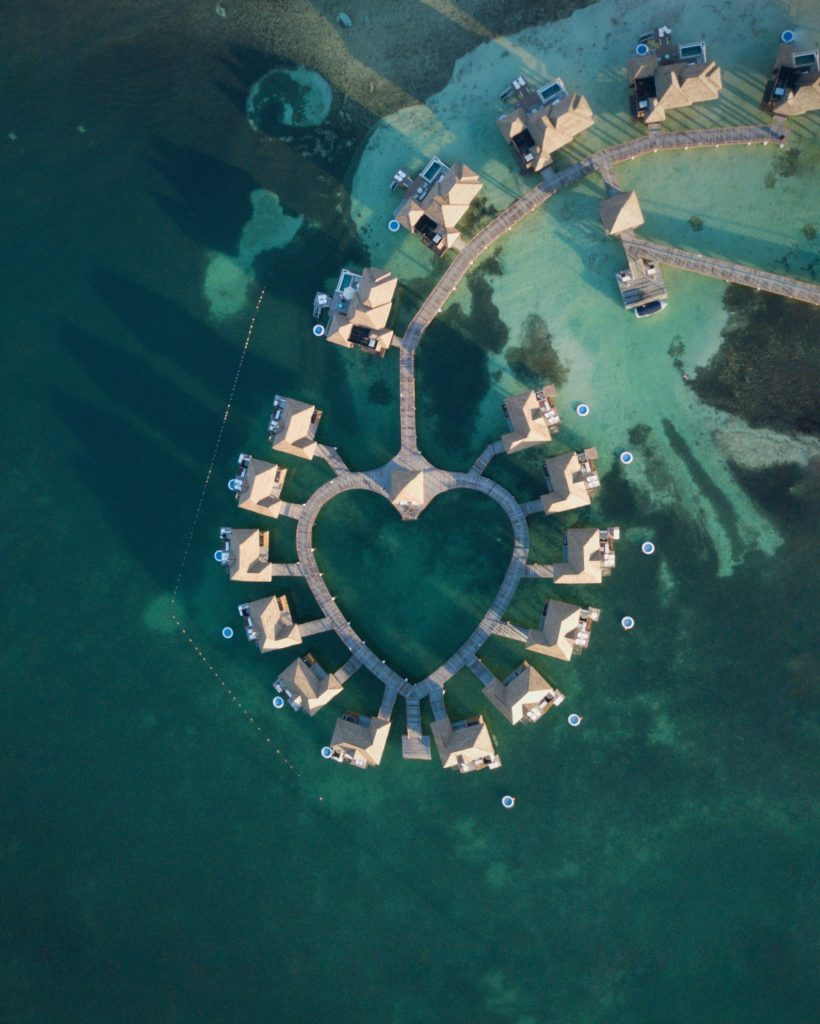 overwater bungalows in heart shape in teal water