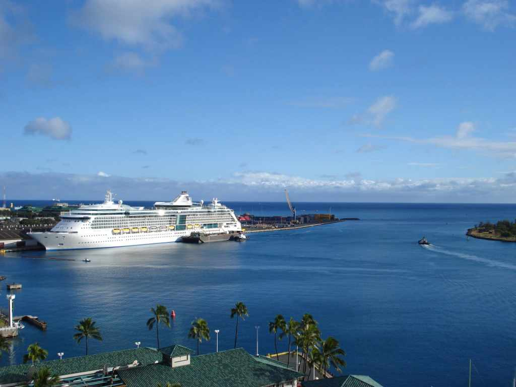 cruise ship docked in ocean port by island