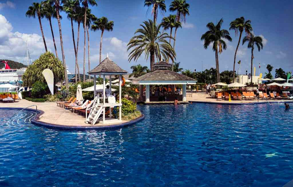 palm trees and resort pool with lounge chairs and outdoor poolside bar