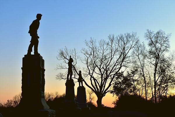 Antietam Battlefield memorials darken as the sun sets behind the trees in Maryland