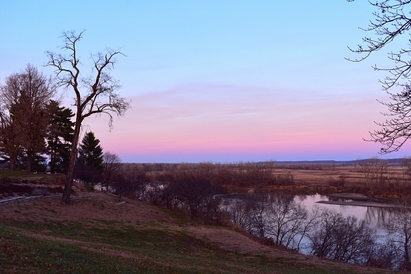 pink sunset sky over a bluff of the Missouri River