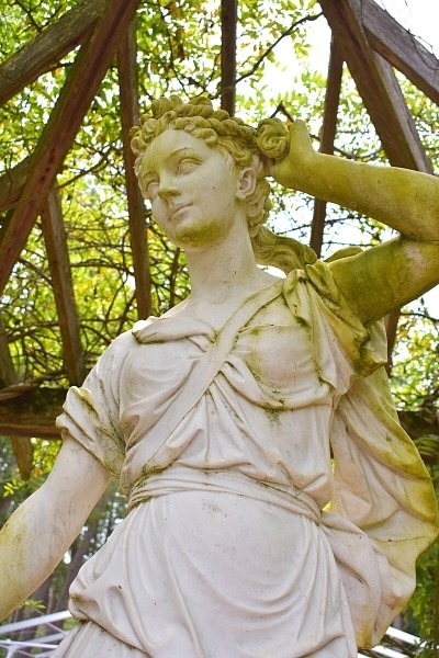 white stone statue of the goddess Diana surrounded by a wooden arbor covered in green leaves