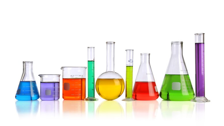 Laboratory glassware with liquids of different colorswith reflections on table