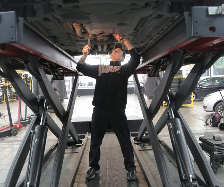 Halfords worker inspects a car