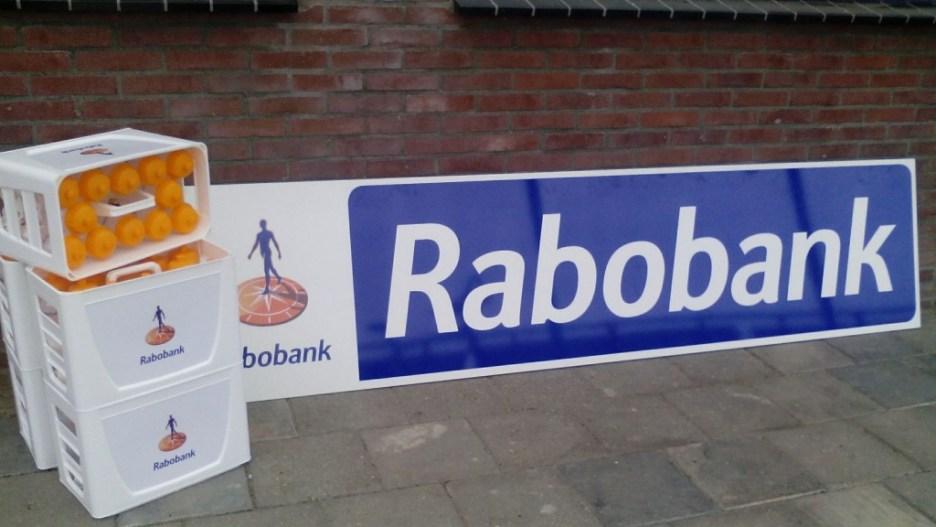 De kratjes met bidonnen en het nieuwe sponsorbord.
