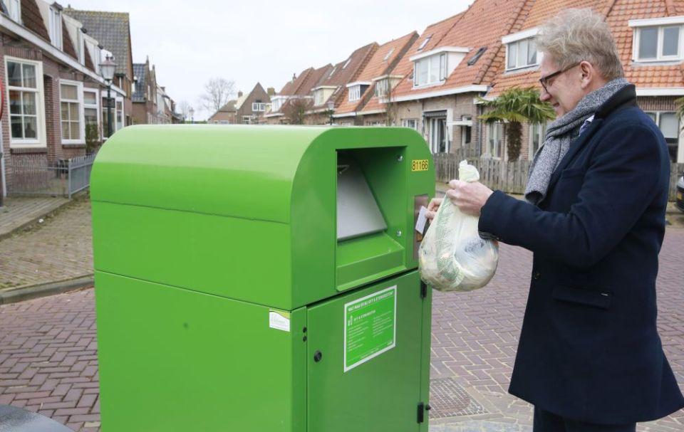 Wethouder Dirk Kuipers gebruikt de afvalpas om de container te openen om zijn biozakje met etensresten weg te gooien.