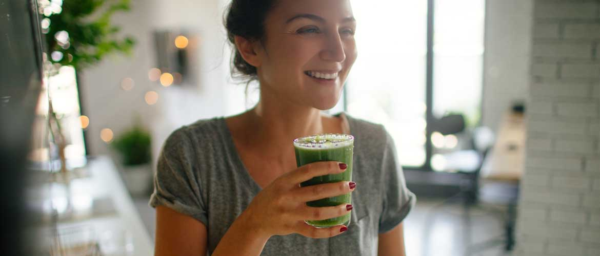 person drinking a green smoothie from a glass