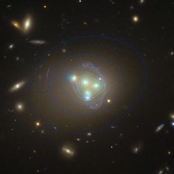 L'immagine  dell'Hubble Space Telescope mostra il ricco ammasso di galassie Abell 3827. Le strane strutture celesti che circondano le galassie centrali sono la vista di una galassia molto più lontana prodotta dall'effetto della lente gravitazionale. La distribuzione della materia oscura nell'ammasso è mostrata con linee di colore blu. Vi è un'estremità di materia oscura per la galassia a sinistra significativamente spostato dalla posizione della galassia stessa, che potrebbe essere prodotto dalla prolungata interazione tra materia oscura.