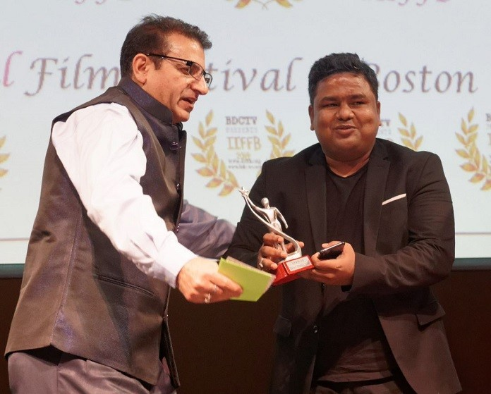 Director Zaigham Imam taking award