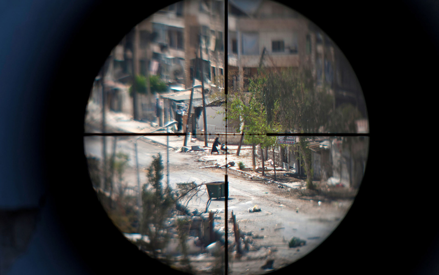 A woman and her baby are seen through the scope of an opposition fighter sniper gun, as she flees the Saif al-Dawla neighbourhood of the Syrian northern city of Aleppo, amid heavy street fighting on August 29, 2012. The battle for Aleppo, Syria's second largest city, has lasted for over a month, with the army unable to dislodge the rebels. AFP PHOTO / ZAC BAILLIE (Photo credit should read ZAC BAILLIE/AFP/Getty Images)
