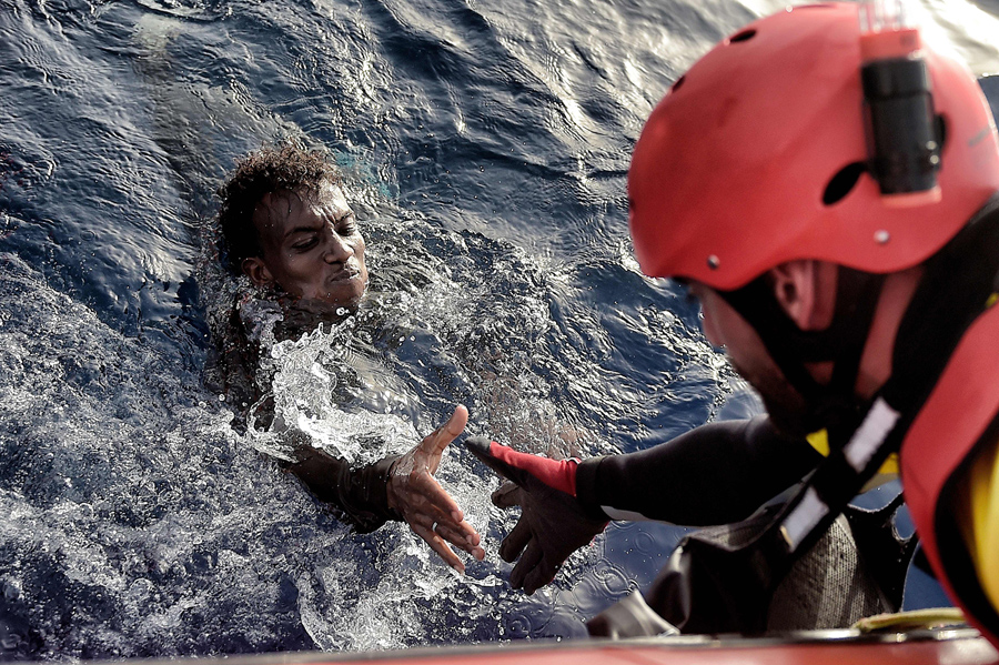 """TOPSHOT - A migrant is rescued from the mediteranean sea by a member of Proactiva Open Arms NGO some 20 nautical miles north of Libya on October 3, 2016. Thousands of migrants are """"racing against the clock"""" to make the perilous crossing from Libya to Europe before summer ends, with authorities in the conflict-torn country at a loss to stem the flow. / AFP / ARIS MESSINIS (Photo credit should read ARIS MESSINIS/AFP/Getty Images)"""