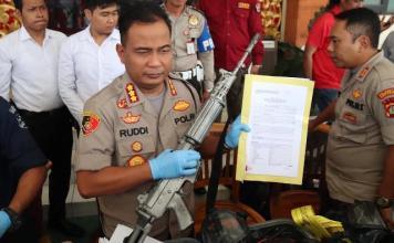 Kapolresta Denpasar Kombes Pol. Ruddi Setiawan memegang senjata api milik anggota Brimob yang hilang
