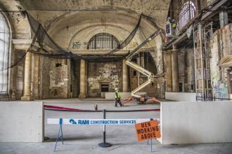 "Inside Michigan Central Station under construction, a decaying archway is featured behind construction tape, a sign that reads ""Men Working Above,"" and a construction worker walking in front of the archway toward a construction machine."
