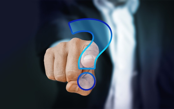 Person pointing to a digitally created question mark.