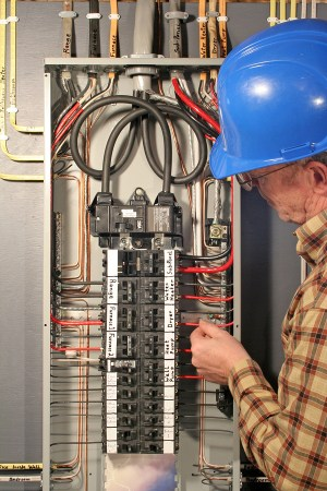 Person working on an electrical panel.