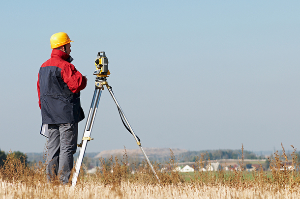 Man in a yellow hard hart surveying on a hill.